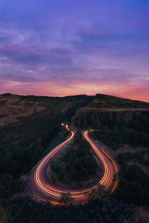 Beautiful vibrant sunset and passing car lights on a horseshoe bend road at Rowena Crest Overlook in Oregon.
