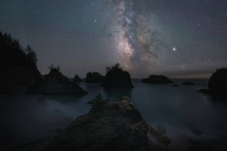 Milky Way Galaxy behind silhouettes of Seas Stacks from Secret Beach Oregon