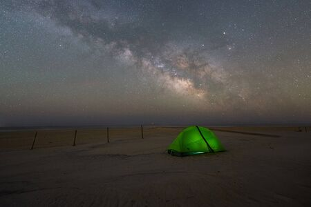 Milky way Galaxy rising over a lit tent