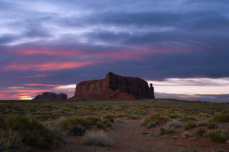 Dirt road leading towards Sentinel Mesa at sunset in Monument Valley Utah