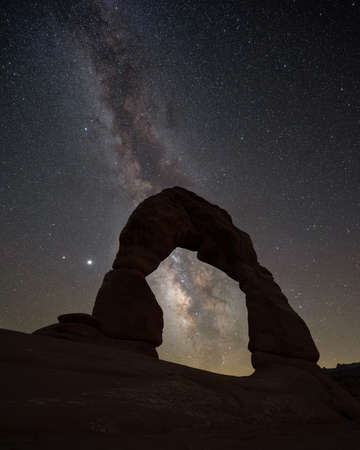 Delicate arch light painted at night under the Milky Way Galaxy in Utah