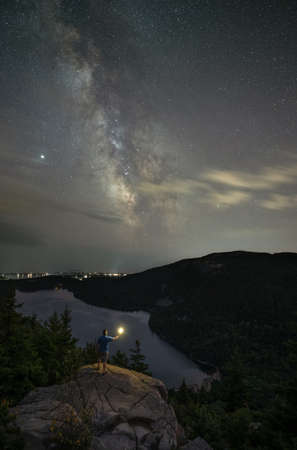 Man standing a ledge over looking Jordan Pond and the Milky Way Galaxy in Acadia National Park Maine