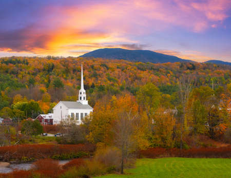 Colorful sky above Stowe Church and autumn trees in Vermont