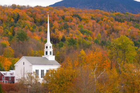White church steeple surrounded by colorful Fall Foliage in Stowe Vermont