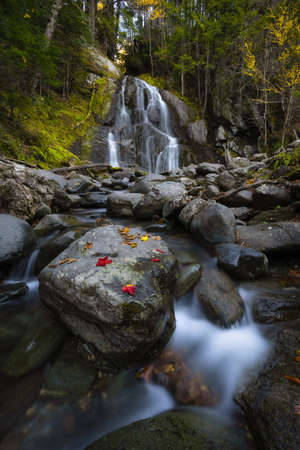 Fall foliage and colorful leaves on a rock in front of Moss Glen Falls in Vermont