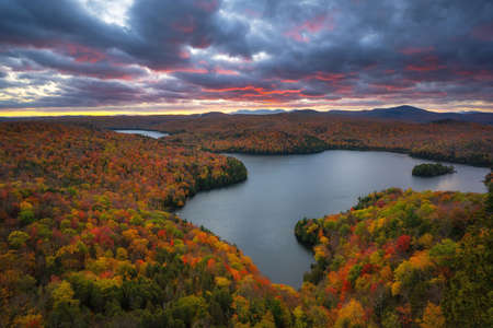 Cloudy sunset over Nichols Pond surrounded by autumn colors in Northern Vermont