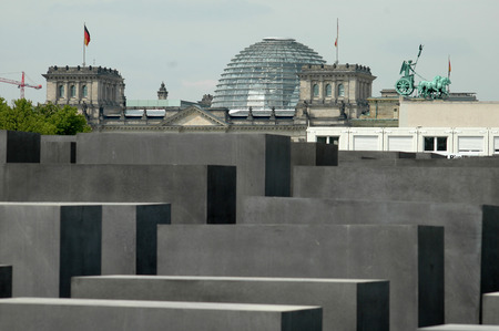 JULY 2005 - BERLIN: Holocaust Memorial, the Brandenburg Gate Quadriga on the, in the background the cupola of the Reichstag, Berlin.