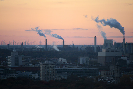 phalanx: Aerial view: view over Berlin, smoking chimneys of a power plant in the background and behind a phalanx of wind power bikes, Sunset, Berlin-Tiergarten.