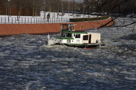 or spree: a boat on the Spree tried to break the ice and make the fairway freely, Berlin-Tiergarten.