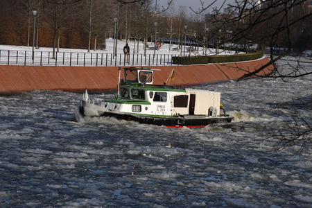 spree: a boat on the Spree tried to break the ice and make the fairway freely, Berlin-Tiergarten.