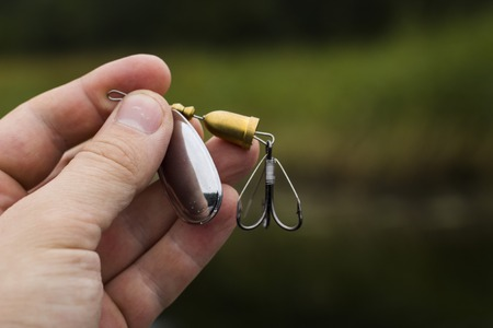 allurement: spinner with a triple hook for fishing in the hand Stock Photo