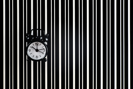 The symbol of the time is the alarm clock on the background of the diffraction bands.Black alarm clock symbolizes time, black diffraction strips on a white background quantum uncertainty Banque d'images - 107452628