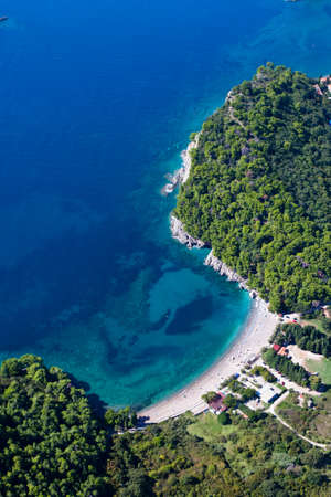 Green paradise bay (bay) among green mountains and the azure sea. landscape below (aerial photo from a paraglider) with the coast and the blue sea, Montenegro, Budva.