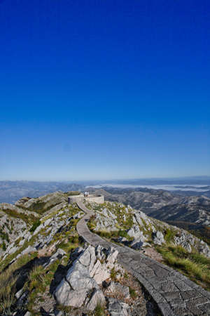 stone path, the road lined with slabs goes along a high pass to the observation deck, blue sky stones and grass summer-autumn landscape. Stockfoto