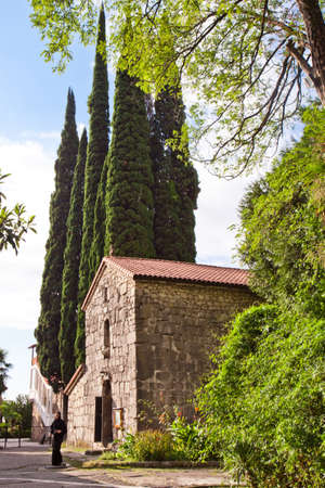 The early Christian Byzantine church against the backdrop of greenery and high cypress trees on the Black Sea coast of the Caucasus. Church of St. Ipatius, Abkhazia, Gagra.
