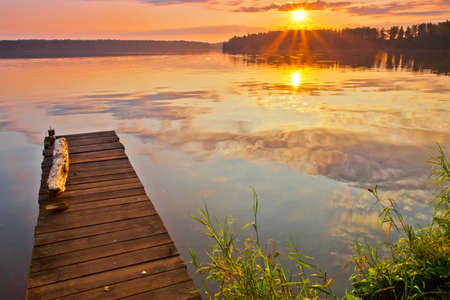 The sun rose. Quiet lake.A small pier (bridge) against the background of the rising sun. Orange - a blue lake landscape.