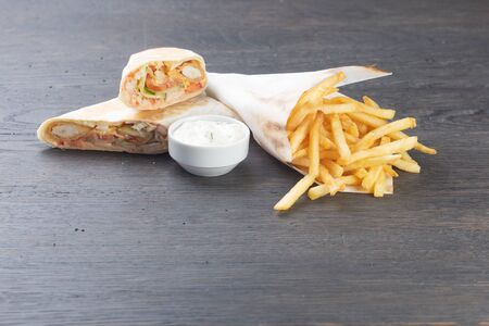 chicken nuggets burrito with pickled cucumbers, tomato, onions and cheese. french fries with cream sauce Standard-Bild - 134947144