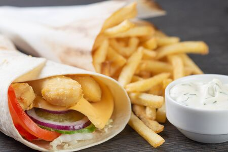 chicken nuggets burrito with pickled cucumbers, tomato, onions and cheese. french fries with cream sauce Standard-Bild - 134947363