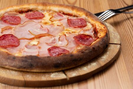 hearty italian pizza on a wooden board. crispy pizza with ham, bacon, salami and cheese sausages