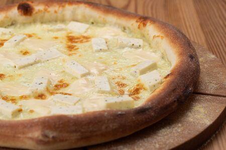 hearty italian pizza on a wooden board. hard cheese pizza