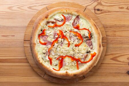 hearty italian pizza on a wooden board. pizza with chicken, pepper, ham and cheese