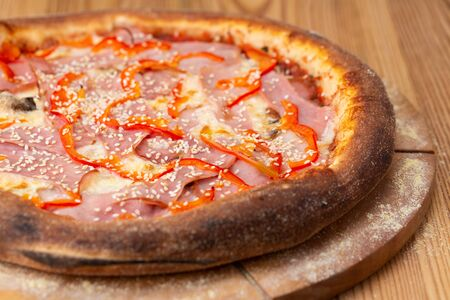 hearty italian pizza on a wooden board. cheese pizza with ham, fresh pepper, mushrooms and sesame seeds Фото со стока