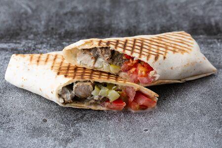 pork roll with tomato and pickled cucumbers. fried pita bread on a stone plate Zdjęcie Seryjne
