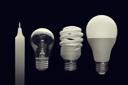 on a dark background from left to right: a candle, an incandescent lamp, a fluorescent lamp, an LED lamp. Banco de Imagens