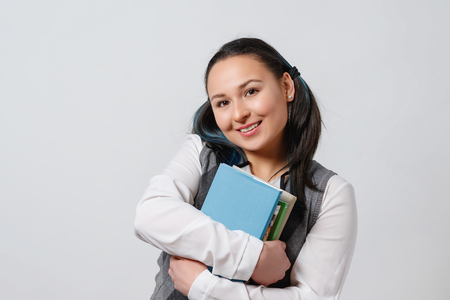 A pretty young girl is a student of a high school student with a stack of textbooks in her hands in front of her. on white background