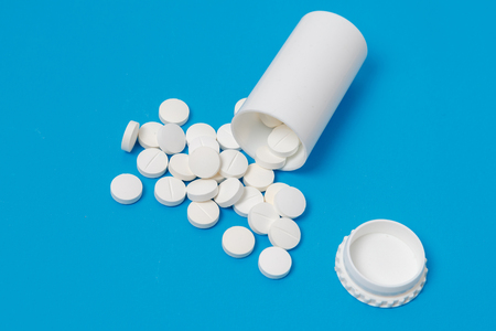 White circle tablets and plastic bottle for tablets on blue background