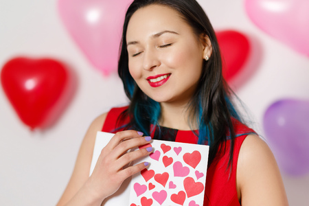 a beautiful young woman takes a card with hearts with a Declaration of love. Valentine's day 14 February