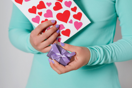 female hands hold a valentine in the form of a paper heart. St. Valentines Day.
