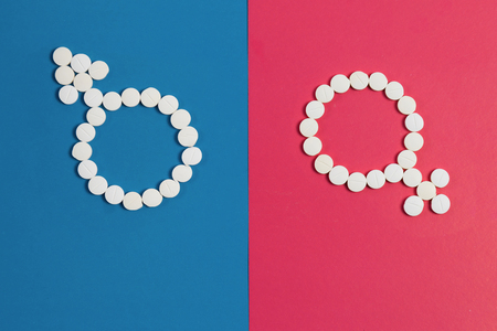 man's sign Mars and Woman's sign Venus made from pink and blue pills on pink background