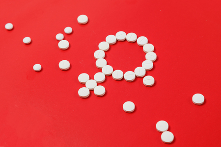 Concept Female health. Gender symbol made from white pills or tablets on red background. Фото со стока