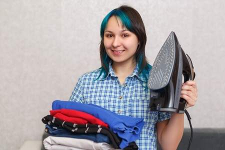 portrait of a beautiful young girl holding a stack of iron and multi-colored linen Stock Photo