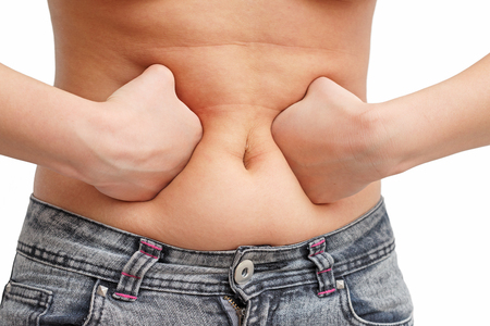 the girl presses the fat on her stomach with two fists inside. front view, white background