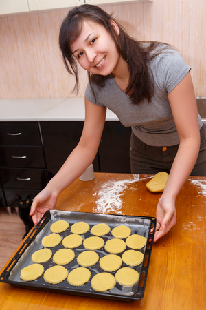 girl in the kitchen holding a baking sheet with blinded cookies for baking
