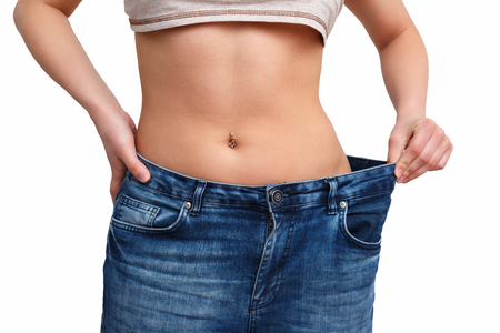 skinny girl in big pants - weight loss concept. isolated on white background