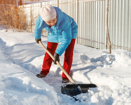 girl cleans snow shovel on the site near his house. sunlight day Фото со стока