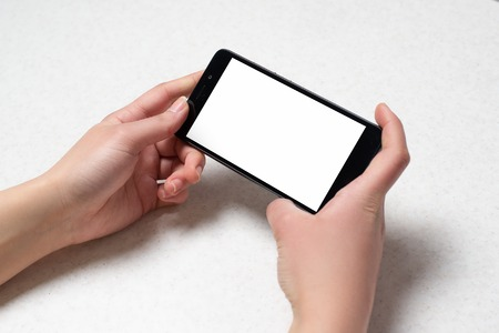 Two hands holding black smartphone , on white background Stock Photo