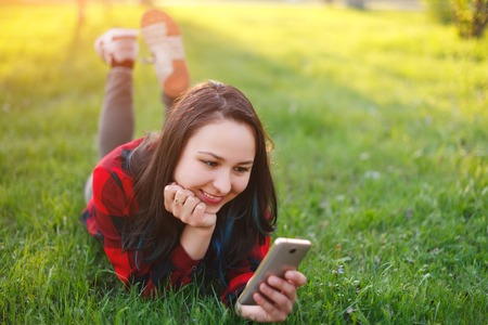 Portrait of a smiling woman lying on green grass and using smartphone outdoors daylight Stockfoto