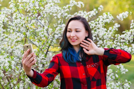 Portrait of a beautiful young woman selfie in the park with a smartphone doing v sign.