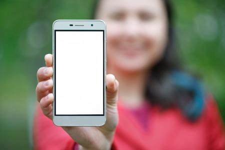 Gros plan d'une femme montrant un écran de téléphone vertical vierge dans la rue