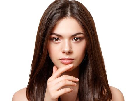 Ritratto di bellezza di una giovane bella ragazza bruna con gli occhi marroni e capelli lisci lunghi e fluenti. isolato su sfondo bianco. Archivio Fotografico