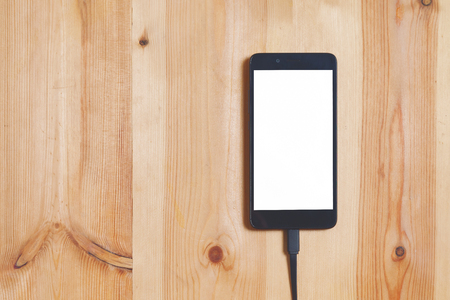 Close up smartphone, and data connecting cable for transfer and Charge battery on the wood floor background and texture use for technology concept.