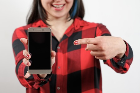 A young girl woman in a red-black shirt is holding a smartphone with a blank black screen vertically in front of her and smiles. Фото со стока