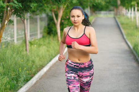 Running woman. Female Runner Jogging during Outdoor Workout in a Park. Beautiful fit Girl. Fitness model outdoors. Weight Loss Stock Photo
