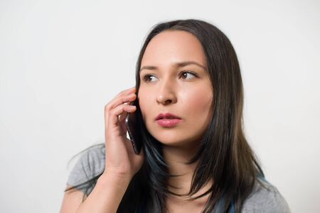 thoughtful young girl talking on the phone and looking away. On white light background