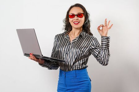 Portrait of a smiling businesswoman holding laptop computer and showing ok. On white background.