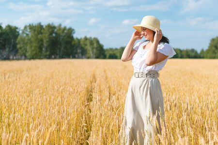 young beautiful woman in golden wheat field. concept of summer, freedom, warmth, harvest, recreation, agriculture